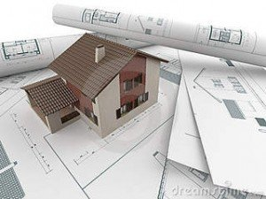 Image of a bundle of architectural drawings with a model of a house