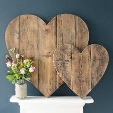 Image of two wooden hearts on a white painted shelf against a grey wall