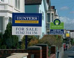 Image of a street with a number of For Sale Boards