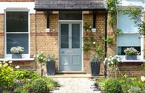 Image of a smart front door painted soft green and with grey planters either side