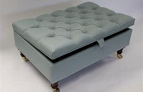 Image of a ottoman style  coffee table with lid that lifts up. It is upholstered in pale blue and the lid is buttoned.l