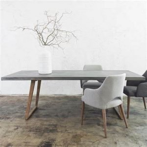 Image of a dining table with slim concrete top and wooden legs with upholstered chairs and a white vase with twigs in