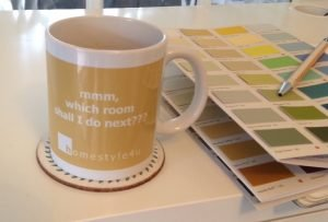 "A yellow mug with the Slogan ""mmm... now which room shall I do next"" on a desk with a paint chart alongside"