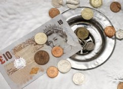 An image of a sink with a £10 note and coins in it to demonstrate wasting money