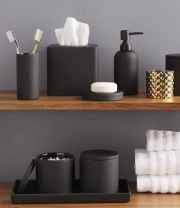 Image of bathroom shelves with selection of accesories including toothbrush holder, soap dispenser  and storage jars in matte black
