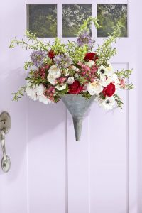 Image of a front door decorated with a metal funnel planted with pretty spring flowers