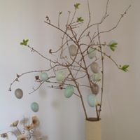 Image of a vase filled with twigs and decorative eggs hung from the branches