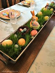 Image of dining table with a plant trough in the middle filled grass and decorated with Easter eggs and an Easter bunny