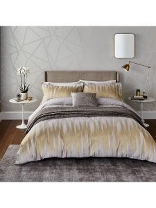 Image of a double bed dressed with bedding in shades of gold and grey to suggest a calm bedroom