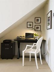 Image of a working area under a flight of stairs including a desk with a laptop on it and a filing cabinet