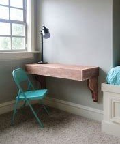 Image of a desk in a corner made from a work surface fitted to shelf brackets