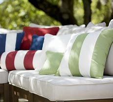 Image of garden seating dressed with colourful striped cushions in maroon, navy and green