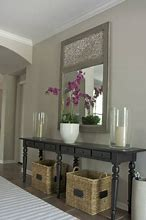 Image of a hallway featuring a console table with mirror above. On the table are two candles and an orchid in a pot. Underneath are two storage baskets.
