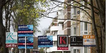 Image of a street with lots of For Sale boards
