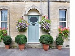 Image of the front of a house with hanging baskets and pots planted with box balls either side of the door.