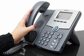 Image of a hand picking up a telephone handset from a desktop system