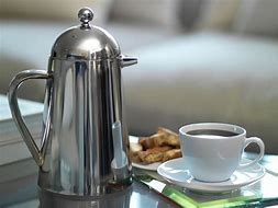 Image of a coffee pot with a cup of coffee and plate of biscuits