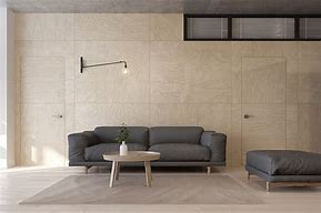 Image of a living room with pale tiled wall, a modern sofa  upholstered in grey and matching ottoman at the side and low pale wood round side table with a round white vase on it positioned in front of the sofa.