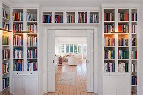 Image of an internal doorway with shelves built round the doorway and filled with books.