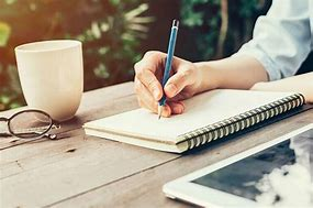 Image of a person writing in a notebook. The image shows the person's arm writing with a pencil. There is a white mug and pair of glasses to the side on the table.