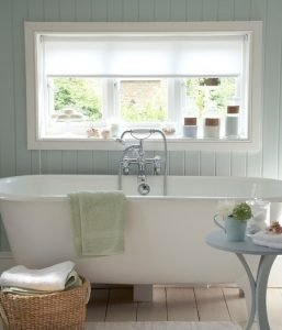 Image of a bathroom showing paneled walls painted in a pale blue/ green and white freestanding bath