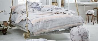 Image of a bedroom featured a bed suspended on rope dressed with a mixture of coastal inspired fabrics