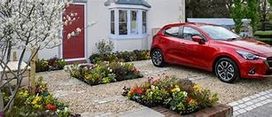 Image of a front garden with a car parked to the right and square beds inset in the drive planted with flowers