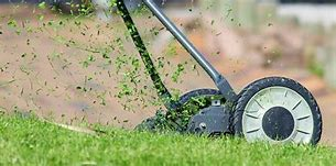 Image of a hand propelled mower with bits of grasses spurting out.