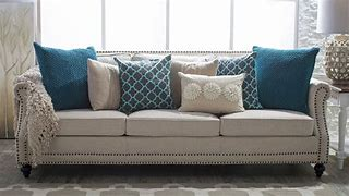 Image of neutral coloured settee dressed with a selection of plain and patterned cushions in teal blue and throw draped over the arm