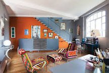 Image of a living room with one wall painted a bright orange and with bold multi coloured furnishings.