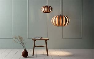 Image of two wooden pendant ceiling lights in the shape of a sea urchin against a backdrop of wooden paneled wall with a stool and vase in front.