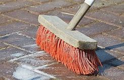 Image of a brush being used to clean a driveway