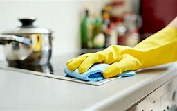Image of a hand in a yellow rubber glovecleaning a kitchen worktop
