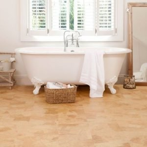 Image of a bathroom showing a white free standing bath on a cork tiled floor. Above the bath is a window with white slatted shutters