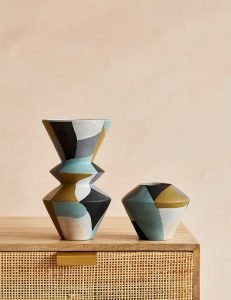 Image of two vases of different shapes and sizes painted in geometric design in shades of ochre, pale blue, black and white