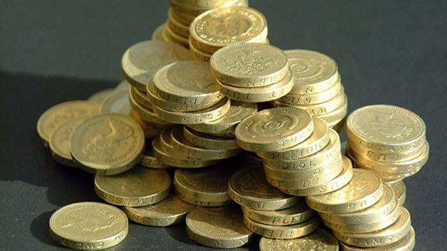 Image of a pile of pound coins against a blue background