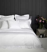 Image of a bedroom showing a bed dressed with white bedlinen with dark grey paneling behind