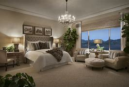 Image of a spacious master bedroom suite with large bed and including a seating area