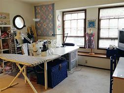 Image of a room laid out for sewing with a table, ironing board and shelving