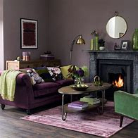 Image of a spohisticated traditional living room with fireplace. The walls are painted grey and there is a a purple sofa, green armchair and a rug on the floor.