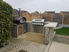 Image of the corner of a garden with a built in pizza oven and bbq