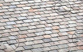 Image of a roof with roof slates that have slipped.