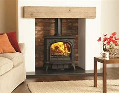 Image of a fireplace with log burner in the brick recess with a wooden beam above