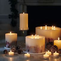 Image of a group of candles of different shapes and sizes all lit.
