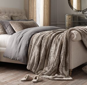 Image of a bed draped with a faux fur throw