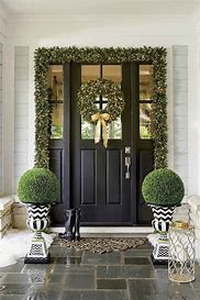 Image of a front door painted black hung with a green and gold wreath and garland and box planters either side