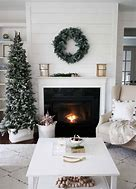 Image of a living room showing a fireplace with Christmas tree to the left and wreath above