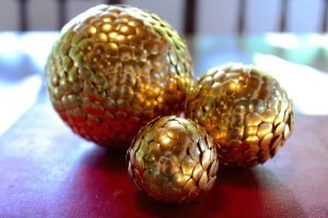 Image of three golden balls of different sizes with scale effect