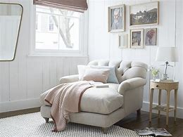 Image of a snuggler chair style chaise with buttoned back in a natural coloured fabric. It is positioned by a window with a side table next to it. The floor is wooden floorboards with a natural textured rug. There is a gallery of five pictures on the wall behind the chair.