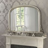 Image of a mirror over  a mantelpiece reflecting light back in to the room. The mirror is a classic silver framed over mantle mirror over a white fire surround and a silver damask type wallpaper behind